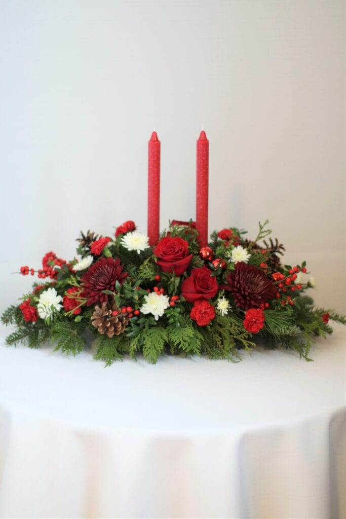 table flower arrangement with pines and red candles